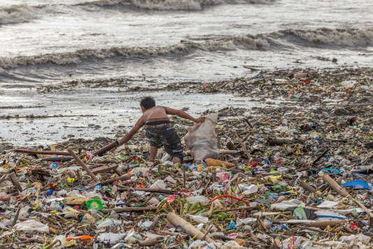 Un homme collecte des plastiques apportés par la mer, à Manille, aux Philippines.
