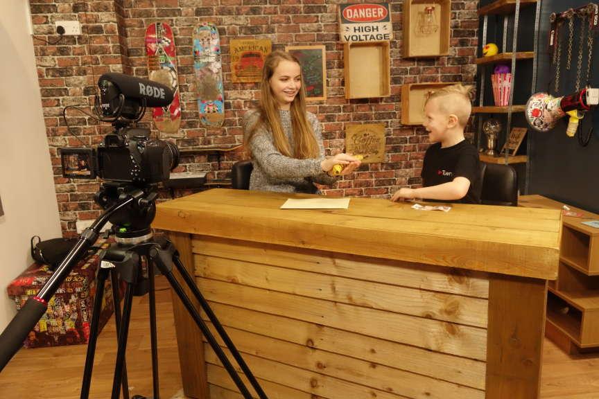 Emily, en plein tournage d'une vidéo de magie avec Blake, le fils du fondateur de l'école.