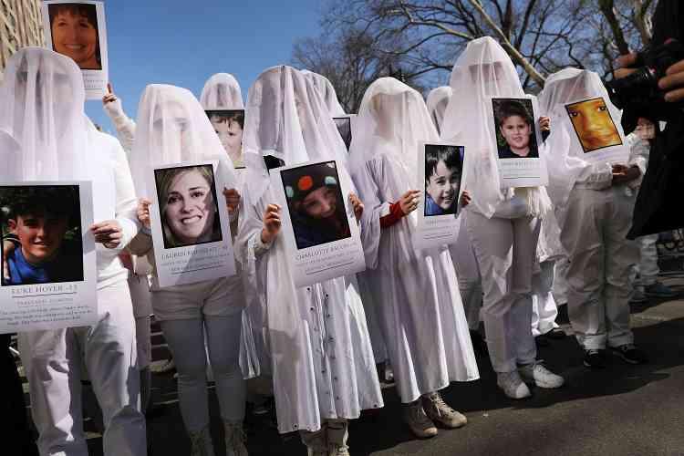 Des manifestants à New York, le 24 mars, montrent les visages de jeunes victimes mortes sous les balles.