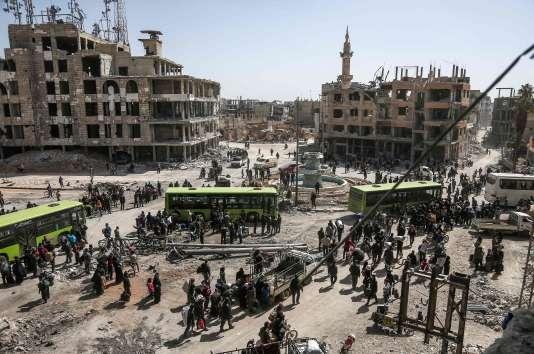 Rebelles et civils s'apprêtent à évacuer la Ghouta orientale, près de Damas, lundi 25 mars.