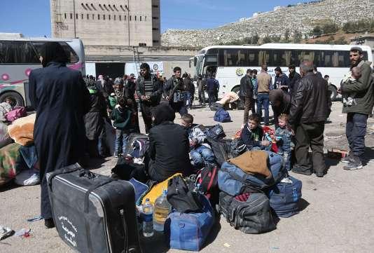 Civils et rebelles évacués de la Ghouta orientale arrivent dans la ville deQalaat al-Madiq, a près de 300 kilomètres au Nord de Damas, mardi 26 mars.