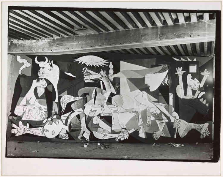 """«Dora Maar photographie les différentes étapes de la création de la grande toile que réalise Picasso pour le pavillon de la République espagnole à l'Exposition internationale de 1937. C'est la première fois que l'artiste accepte une collaboration aussi intime avec une photographe. Chaque épreuve, développée au fur et à mesure de l'avancée du travail, fige un instant de la composition et constitue ainsi un témoignage unique du processus créatif de la toile. L'ensemble des photographies est immédiatement publié dans un numéro exceptionnel de la revue """"Cahier d'art"""", entièrement consacré à """"Guernica"""".»"""