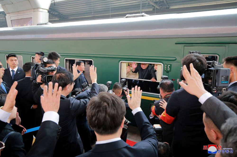Kim Jing-un et son épouse saluant la délégation chinoise alors que leur train quitte le quai, mardi 27 mars.