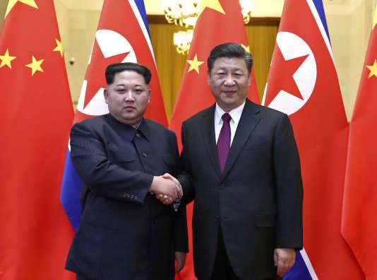 L'agence de presse Xinhua a publié mercredi 28 mars une photo montrant la poignée de main de Kim Jong-un et de Xi Jinping devant les drapeaux des deux pays.