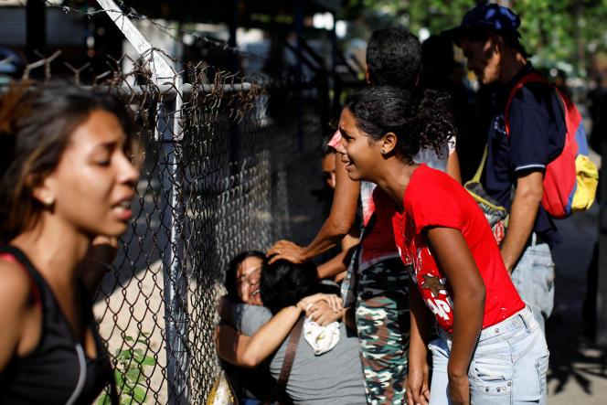 Des proches de détenus, devant les grilles du commissariat principal de Valence, dans l'Etat de Carabobo au Venezuela, le 28 mars.