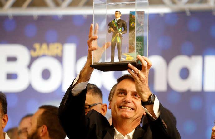 Jair Bolsonaro montre une poupée à son effigie lors d'un meeting à Curitiba, le 29mars 2018.