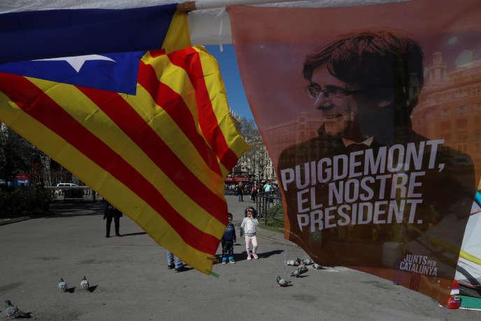 Un drapeau catalan flotte à côté d'une affiche de soutien à Carles Puigdemont, le 28 mars, à Barcelone (Espagne).