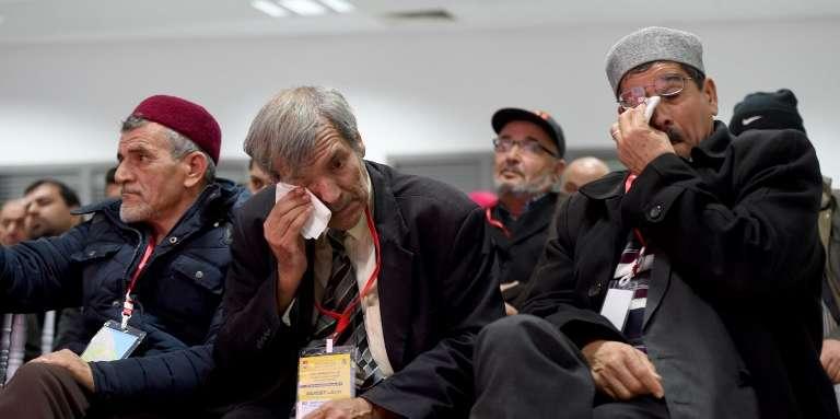 Des hommes regardent la retransmission à la télévision des témoignages de victimes d'abus devant la Commission vérité et dignité, à Tunis, le 16décembre 2016.