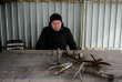 Le fils d'Elena, Andrei, pose devant des munitions et des fragments retrouvés dans son jardin et sur le toit de sa maison. Il vit au numéro 112 de la rue Lénine.