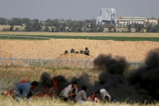 Des Palestiniens se cachent des snipers israéliens slors d'affrontements à la frontière sud de la bande deGaza, samedi 31 mars.