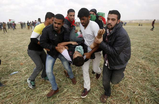 Un blessé palestinien évacué après les tirs des forces israéliennes, à la frontière de la bande de Gaza avec Israel, le 30 mars.