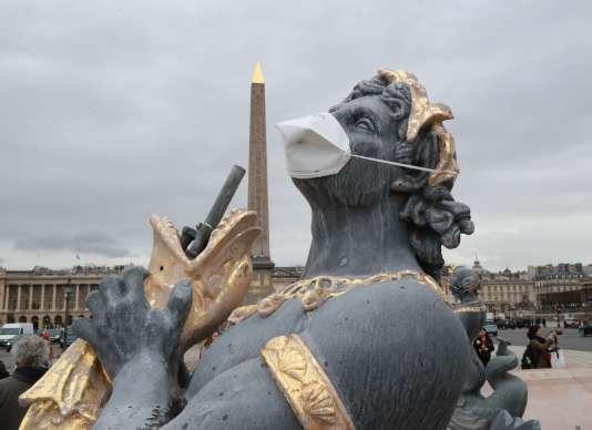 Place de la Concorde, à Paris, une statue avec un masque lors d'une manifestation contre la pollution, le 31 mars.