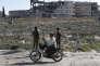 Un Syrien passe devant des membres des forces kurdes, le 31 mars à Manbij (nord de la Syrie).