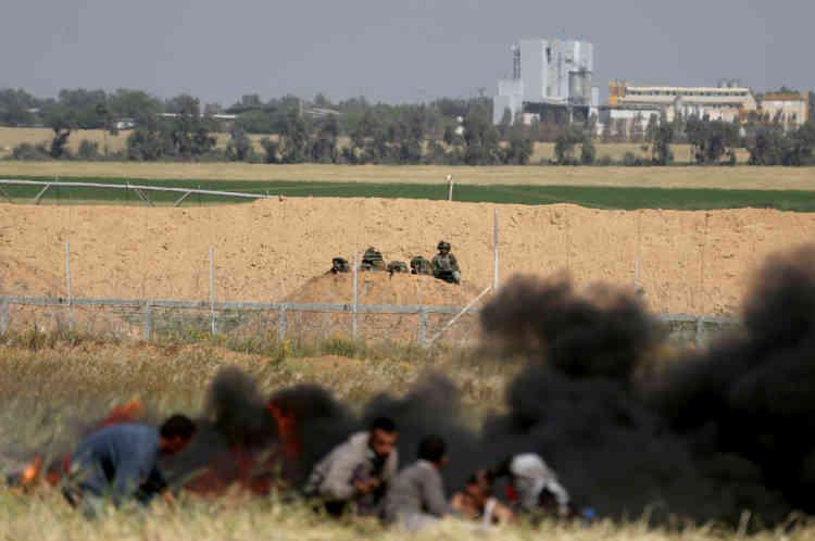 Des manifestants palestiniens se cachent des soldats israéliens, samedi 31 mars.