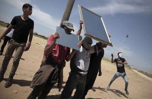 Des manifestants palestiniens tentent d'éblouir les soldats israéliens en brandissant des miroirs, lundi 2 avril, à Gaza.