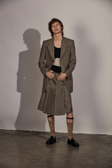 Veste et jupe de kilt en laine imprimée Prince-de-Galles, porte-chaussettes et chaussettes en coton, Gucci. Top en nylon, Lacoste. Mocassins en cuir, Church's.