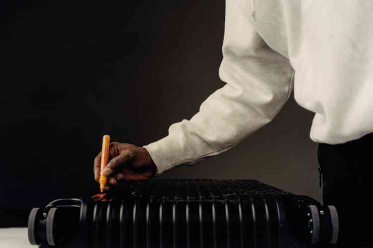 Pull en coton, Dust. Valise rigide en aluminium noir, Rimowa.