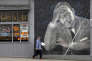 A man walks past a large mural of the Rev. Martin Luther King Jr. on the side of a diner, painted by artist James Crespinel in the 1990's and later restored, along Martin Luther King Jr. Way, Tuesday, April 3, 2018, in Seattle. The civil rights leader was killed 50 years ago Wednesday in Memphis. Seattle events commemorating his assassination will be held Wednesday evening at Mt. Zion Baptist Church. (AP Photo/Elaine Thompson)