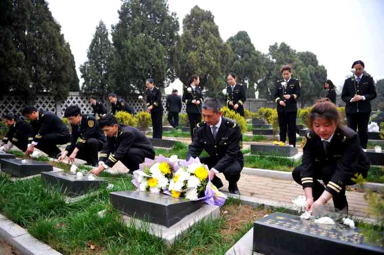 Des membres du personnel du Qingdao Jiaoyun Group, une société de transport, déposent des fleurs dans un cimetière de Qingdao, le 3 avril.