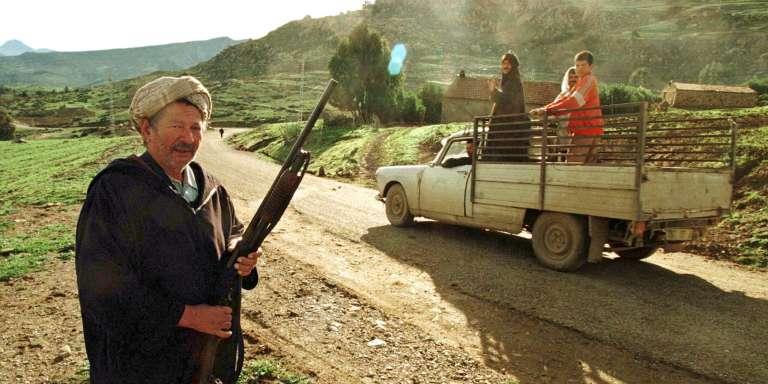 Un homme armé d'un fusil sur une route menant à son village, victime d'un massacre perpétré par le Groupe islamique armé qui a coûté la vie à 412 personnes, le 30 décembre 1997.