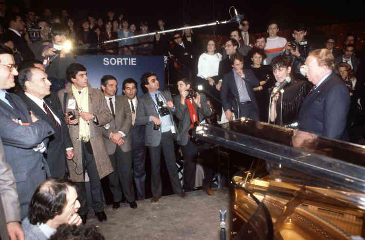 Le président François Mitterrand (à gauche) écoute Charles Trenet et Jacques Higelin interpréter en duo «Qu'il est beau le bruit de l'eau», lors de la soirée d'inauguration du Zénith à Paris, le 12janvier 1984.