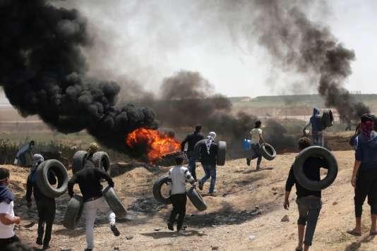 Des Palestiniens fontbrûler des pneus pour ne pas être vus distinctement par les tireurs israéliens, à la frontière entre la bande de Gaza et Israël, le 6 avril.