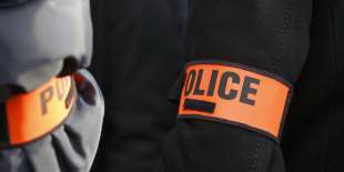 """Police officers wearing masked armbands take part in a protest outside the headquarters of the Inspection Generale de la Police Nationale (General Inspectorate of the National Police, IGPN), a sub-directorate responsible for internal affairs, as one of their collagues is being heard on November 3, 2016 in Paris. Several hundreds of police officers demonstrated on November 3 outside the headquarters of the IGPN, the dreaded """"police of the police"""", where Guillaume Lebeau, a leader of police demonstrations which have continued and spread for nearly three weeks, was being heard. Police in France have been complaining for weeks against an ever-increasing workload, bureaucracy, outdated equipment and what is seen as lenient sentencing for violence against officers. / AFP PHOTO / PATRICK KOVARIK"""