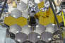 Space Telescope UncoveredInside the cleanroom on the afternoon of April 25, 2016 - James Webb Space Telescope primary mirrors being uncovered at NASA Goddard in preparation for instrument installation.Why are we taking the JWST mirror covers off? The covers are just lightly fastened and protect the mirrors while they are face up. We'll rotate JWST so the mirrors are face-down to install the instruments behind the primary mirror. Thus the covers are coming off.