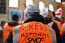 A rail worker wearing a SNCF high visibility vest with the words, 'reform strike' , takes part in a rally called by the French trade union the General Confederation of Labour (CGT) at the Saint-Charles train station in the southern coastal city of Marseille on April 4, 2018, on the second day of three months of rolling rail strikes. Staff at French state rail operator SNCF walked off the job from 7.00 pm (1700 GMT) on April 2, the first in a series of walkouts affecting everything from energy to garbage collection. The rolling rail strikes, set to last until June 28, are being seen as the biggest challenge yet to the President's sweeping plans to shake up France and make it more competitive. / AFP PHOTO / BERTRAND LANGLOIS