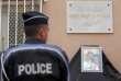 Le 15 juin 2016, un policier se tient face à la photo des deux agents assassinés à leur domicile à Magnanville.