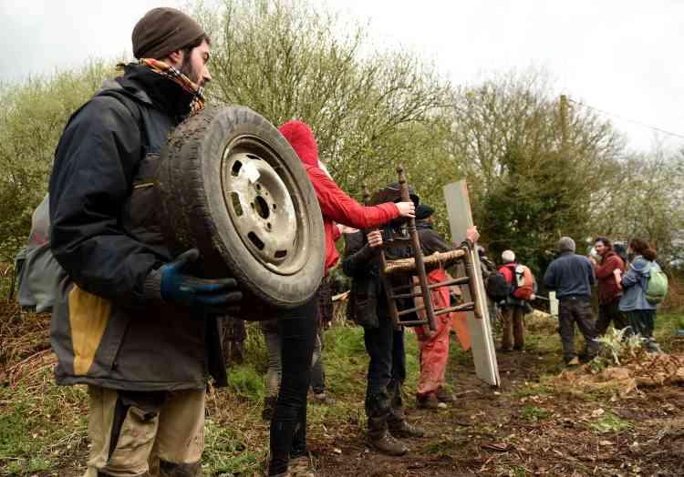Les zadistes forment une chaîne pour construire une barricade pour protéger Les Vrais rouges, un des lieux de la ZAD.
