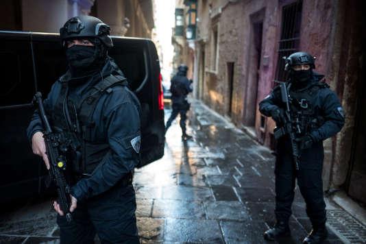 Des policiers protègent l'entrée arrière du palais de justice de La Valette à Malte, le 26 mars, lors de l'arrivée des assassins présumés de la journaliste Daphne Caruana Galizia.