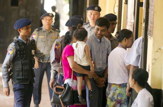 Le journaliste de Reuters Kyaw Soe Oo salue son éspouse Chit Su Win et sa fille lors de son arrivée au tribunal à Rangoun le 11 avril.