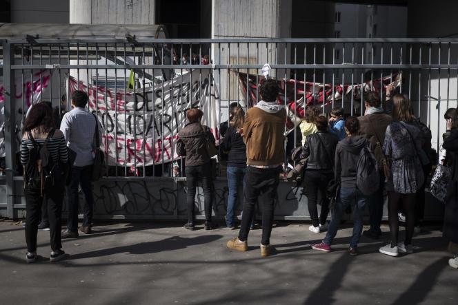 Étudiants, passants, et curieux regardent à travers la grille lors d'une AG organisé par le comité de mobilisation a la faculté de Tolbiac, le 11 Avril 2018.