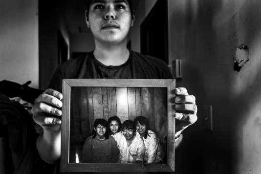 Le fils de Vanessa Napoleon tient dans ses mains une photo de sa mère (à gauche), sa grand-mère et ses deux tantes dont Pamela (à droite).