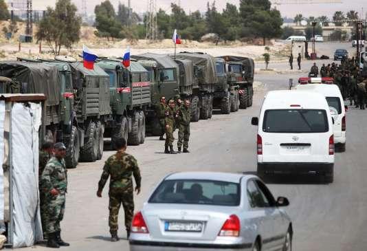 Soldats russes et syriens attendent l'arrivée de combattants rebelles évacués de la Ghouta orientale.