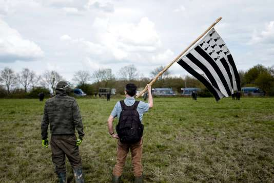 Claude K. arpente la zone, tête nue, à visage découvert, porteur d'un «Gwen ha du», le drapeau de la Bretagne.