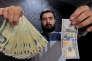Dans un bureau de change de Téhéran en janvier 2016, un employé pose avec un billet de 100 dollars et l'équivalent en rials.