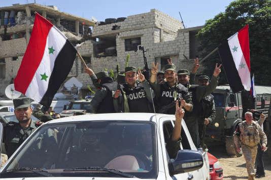 Des policiers syriensagitent le drapeau national aux portes de Douma, dans la Ghouta orientale, le 14 avril 2018.