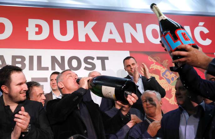 Milo Djukanovic fête sa victoire au champagne au siège de son parti à Podgorica, dimanche soir.