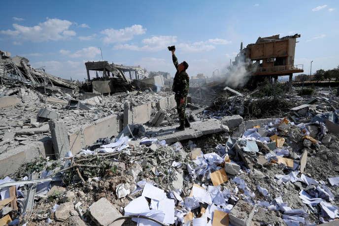 Un militaire syrien filme les dégâts occasionnés au centre d'étude et de recherche syrien (CERS), a proximité de Damas, après les raids américains, britannique et français, le 14avril 2018.