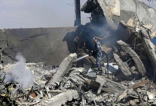 Un soldat syrien éteint les flammes dans les décombres du Centre d'études et de recherches scientifiques (SSRC), à Damas, le 14 avril.