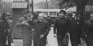 Charles Maurras, entouré de ses gardes du corps, entre au Palais de justice à la suite de ses appels au meurtre de Léon Blum, Paris, 1936.