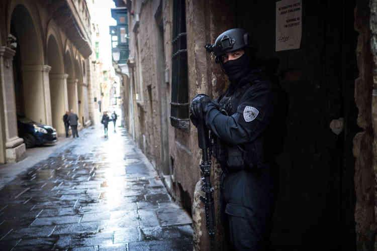 Des policiers protègent l'entrée arrière du palais de justice de LaValette lors de l'arrivée des assassins présumés, le 26mars2018.En vertu du système judiciaire maltais, les preuves sont présentées tout au long de l'instruction, lors d'auditions publiques, où médecins, policiers, militaires intervenus sur la scène du crime et témoins sont appelés à la barre. Ils jurent de dire la vérité, en embrassant un imposant crucifix, placé à côté d'un micro.