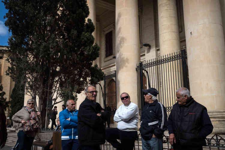 Des personnes discutent devant l'entrée principale du palais de justice lors d'une audience de comparution des assassins présumés.Suivie en direct par tous les sites d'information du pays, l'instruction de l'assassinat de Daphne Caruana Galizia n'est pas seulement le plus gros dossier criminel depuis des décennies à Malte, il est celui qui suscite le plus de passions.
