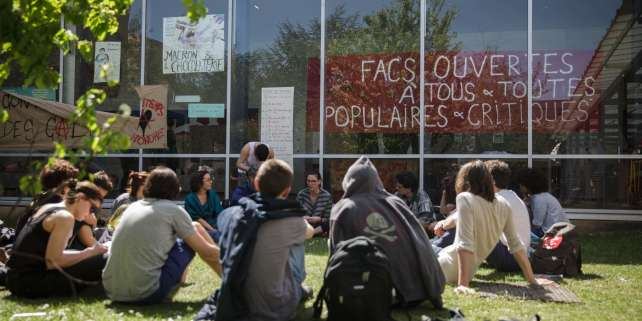 "Protesting students gather on the campus of the Nanterre University, west of Paris, on April 18, 2018 as part of nation-wide demonstrations against higher education reforms, introduced by the French government that give public universities the power to set admission criteria and rank applicants. The banner reads ""Universities are open to all, are popular and open to critics"". / AFP / -"