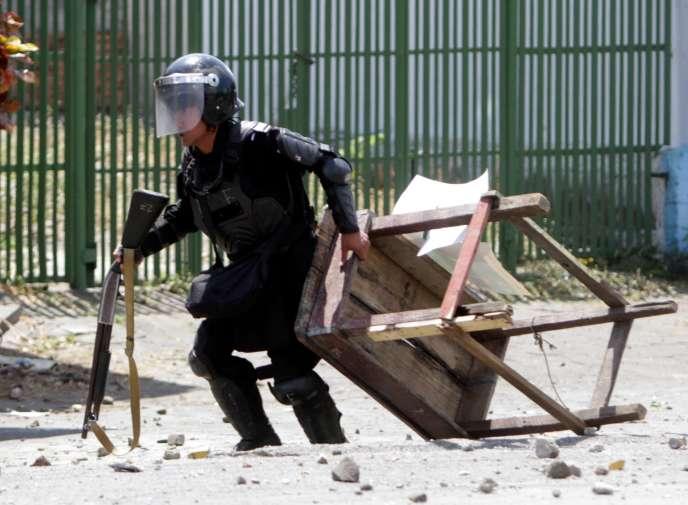 Un policier tente de retirer les barricades àManagua, le 19 avril 2018.