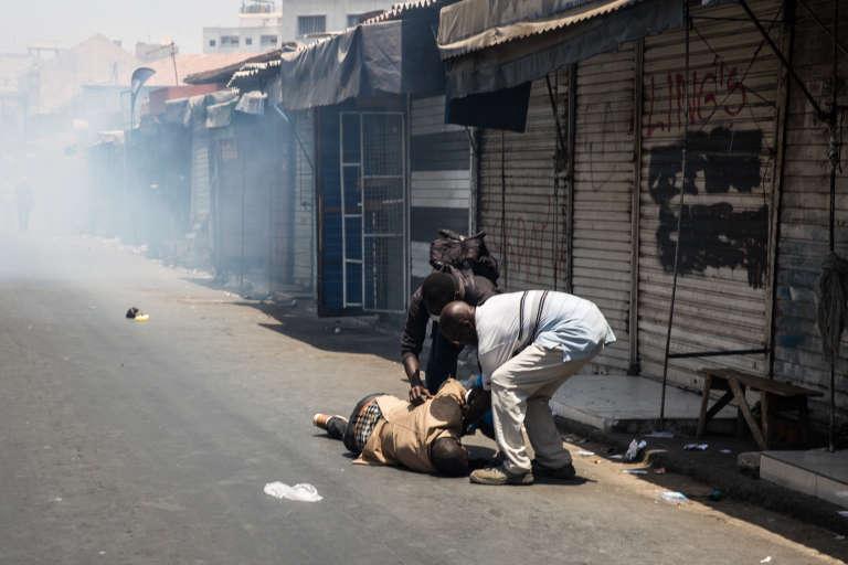 Un homme blessé par une grenade lacrymogène est aidé par deux personnes dans les rues de Dakar près du marché Sandaga, le 19 avril.