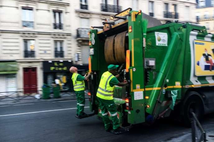 Frédéric et Yoan, sur le marchepied à l'arrière de la benne à ordures, lors d'une collecte de déchets, le 18avril, à Paris.