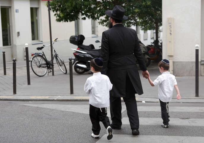 Un homme juif tenant la main à deux enfants, le 4 juillet 2009, à Paris.